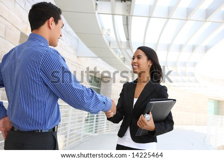 Attractive man and woman business team shaking hands at office building - stock photo