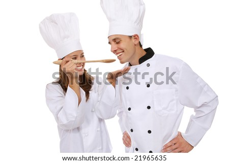 Attractive man and woman chef tasting food - stock photo