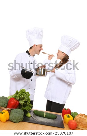 Attractive man and woman chefs cooking and tasting food - stock photo