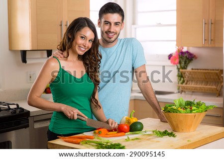 Attractive man and woman prepping low calorie dinner in kitchen very health conscious - stock photo