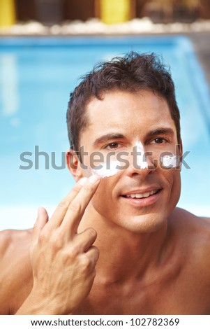 Attractive man applying sunscreen to his face with his finger - stock photo