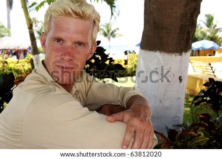 Attractive Man at beach looking at camera - stock photo