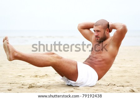 Attractive man doing fitness workout on the beach - stock photo