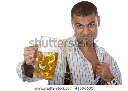Attractive man dressed in leather trousers (Lederhose) holds Oktoberfest beer stein and opens a little his shirt. Isolated on white. - stock photo
