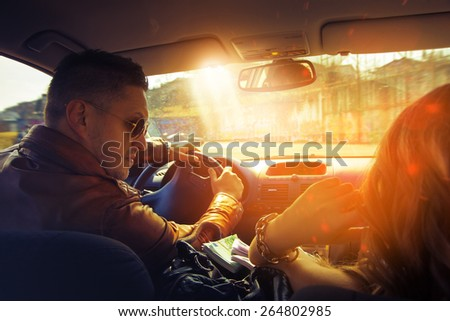 Attractive man driving car and look at his girl. Inside photo - stock photo