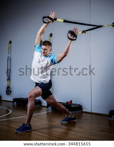 Attractive man during workout with suspension straps In The Gym's Studio