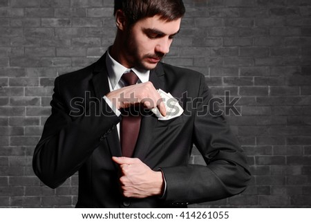 Attractive man getting dollar banknotes out of suit pocket on brick wall background