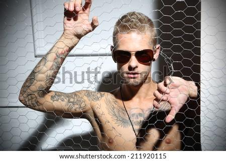 Attractive man . Handsome tattooed Caucasian man rips the mesh,  - stock photo