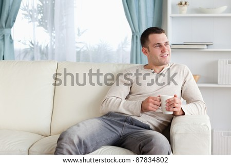 Attractive man having a coffee in his living room - stock photo