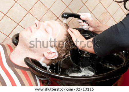 Attractive man having a shampoo in a hairdressing salon - stock photo