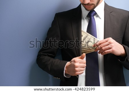 Attractive man hiding dollar banknotes in suit on blue background - stock photo
