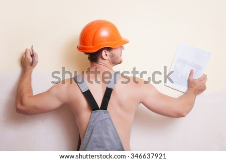 Attractive man in a helmet. Pen and paper in a hands. - stock photo