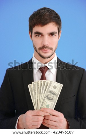 Attractive man in a suit holding fan of dollar banknotes on blue background - stock photo