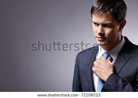 Attractive man in a suit straightens his tie - stock photo
