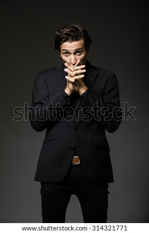 attractive man in black suit on dark background acting - stock photo