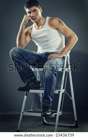 attractive man in jeans sitting on stairs - stock photo