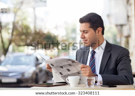 Attractive man in suit is sitting at table in cafe outdoors. He is reading newspaper with interest and smiling. The worker is drinking tea. Copy space in left side - stock photo