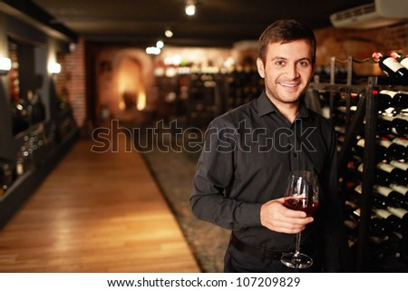 Attractive man in the wine cellar - stock photo