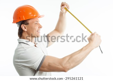 Attractive man is holding tape-measure in his arms. He is smiling and looking at it with interest. The foreman has helmet on his head. Isolated on background - stock photo