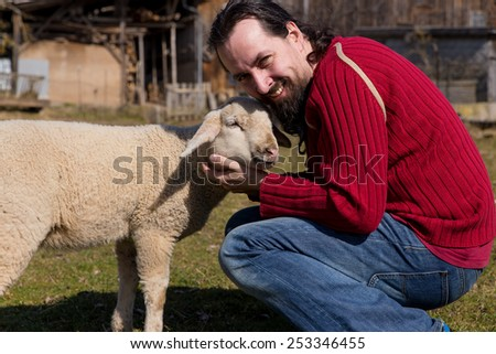 Attractive man is hugging a cute lamb - stock photo