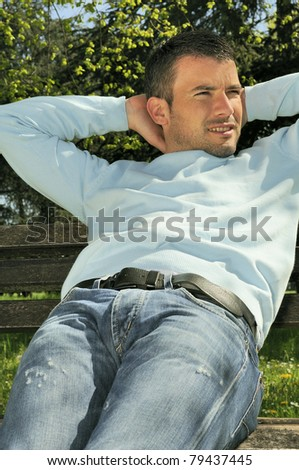 attractive man is relaxing on a bench in a natural environement - stock photo