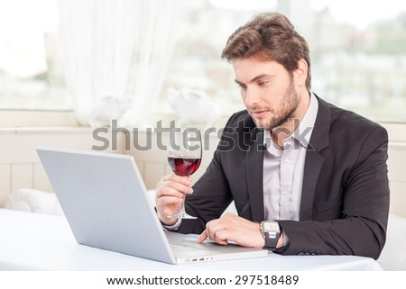 Attractive man is working on his project in his notebook with seriousness. He is sitting at the table in restaurant and drinking wine - stock photo