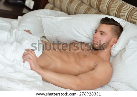 Attractive man lying in his bed - stock photo
