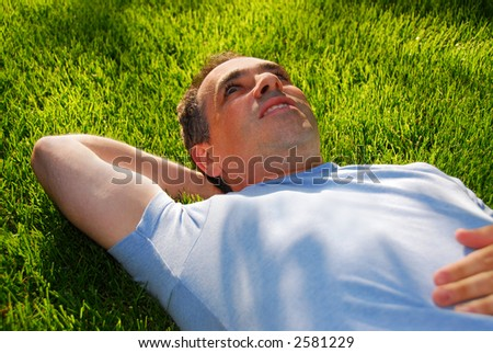 Attractive man lying on green grass in a park relaxing