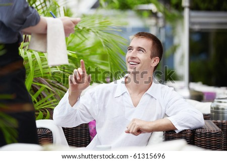 Attractive man makes an order in a restaurant - stock photo