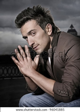 Attractive man posing and looking to the camera outdoor - stock photo