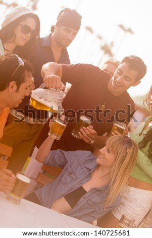 Attractive Man pouring a beer at an outside cafe on the Beach in Venice California - stock photo