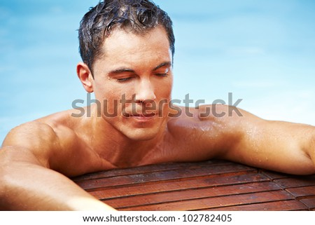 Attractive man relaxing in swimming pool with blue water - stock photo