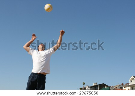 Attractive man serving a volleyball at beach
