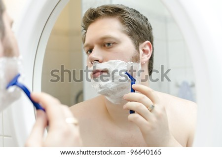 Attractive man shaving in bath room - stock photo