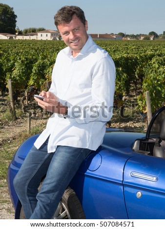 Attractive man sits in cabriolet in countryside writting message at his smartphone with a smile