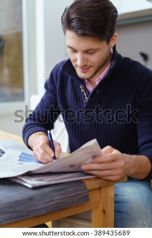 Attractive man sitting at a table at home checking newspaper adverts for employment or accommodation marking interesting ones with a pen