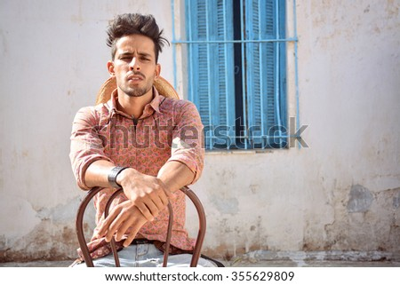 attractive man sitting on chair  - stock photo