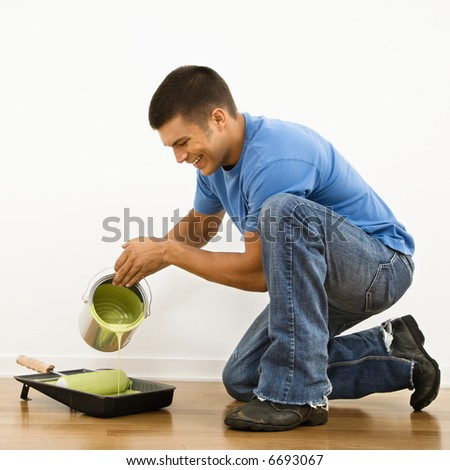 Attractive man smiling and pouring paint into roller pan in home.