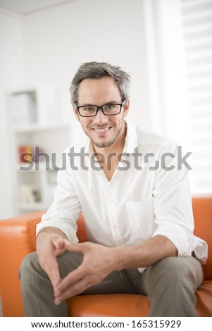 attractive man smiling on a couch - stock photo