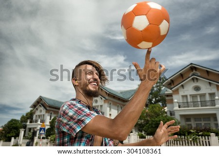 Attractive man spinning a ball on his finger on the street - stock photo