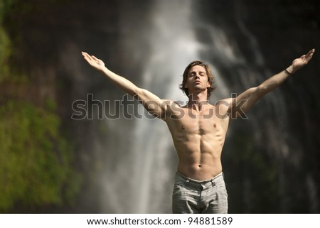 Attractive man standing by waterfalls with arms outstretched in the air. - stock photo