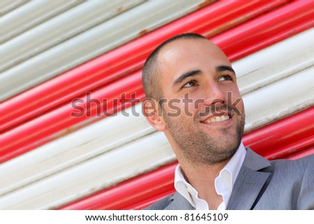 Attractive man standing on subway striped background
