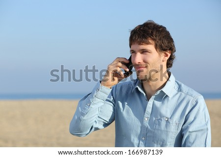 Attractive man talking on the phone on the beach isolated on a white background             - stock photo