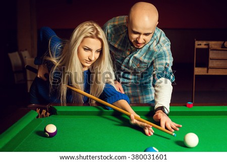 attractive man teaches Woman begins the game on the pool table. Billiard sport concept. American pool billiard. Pool billiard game. - stock photo
