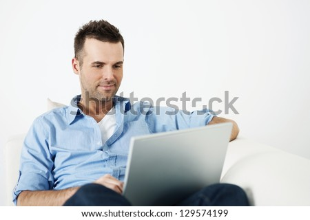 Attractive man using laptop on sofa