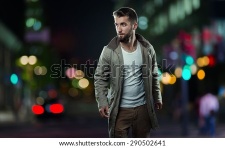 Attractive man walks alone through the streets of the city at night - stock photo