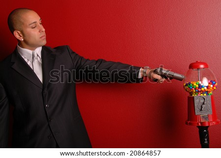 Attractive man wearing a business suit pointing a gun at a gumball machine. - stock photo