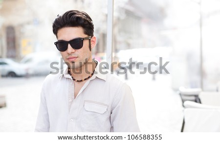 attractive man wearing sunglasses looking cool on the street - stock photo
