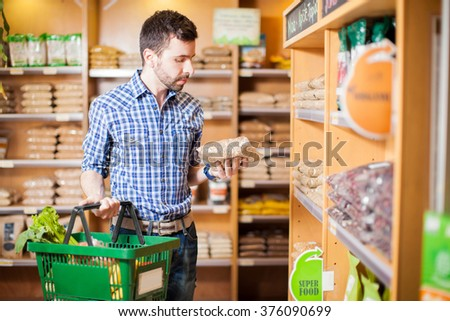 Attractive man with a beard reading a product label while buying groceries at a store - stock photo