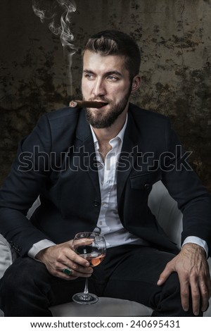 Attractive man with a cigar and a drink - stock photo